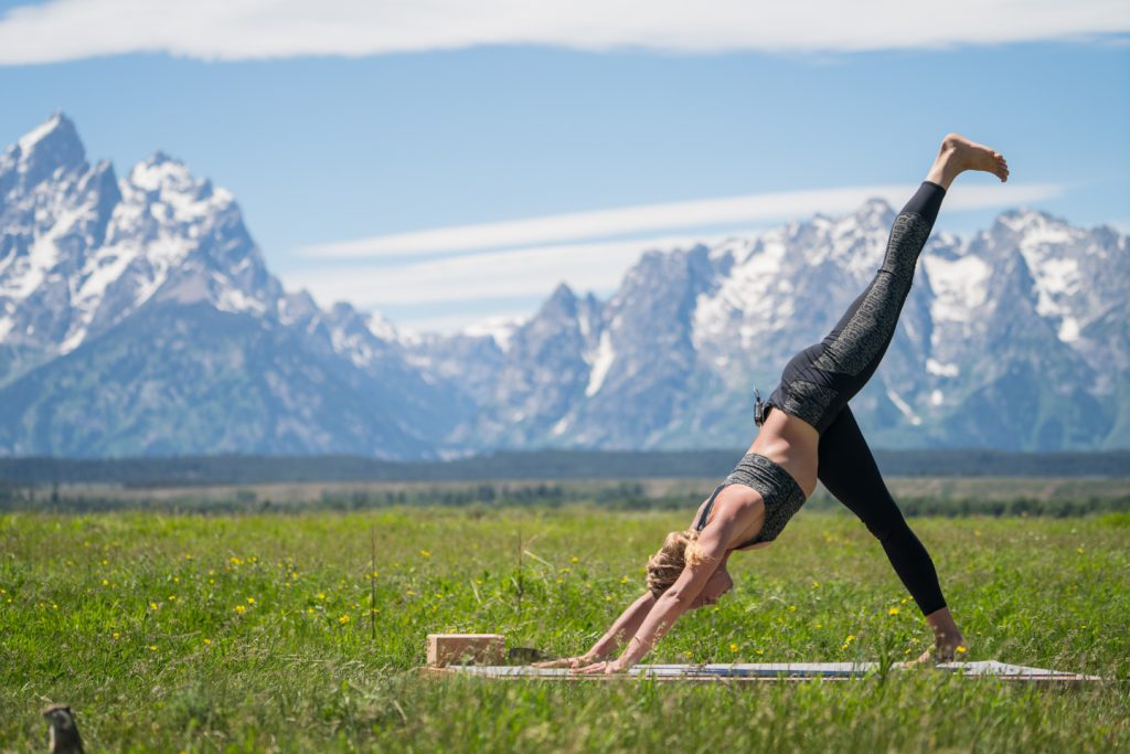 woman practices downward facing dog - yogatoday