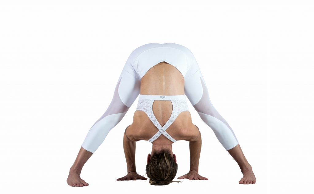 woman practices wide legged forward fold yoga pose -yogatoday